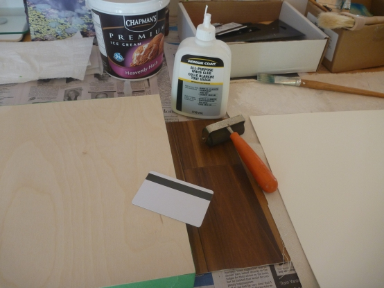 I use a scraper to move the glue all across both surfaces and then attach the paper onto the panel. The roller is used to roll the paper after it is glued. I put a heavy book onto the panel and leave it to dry overnight.